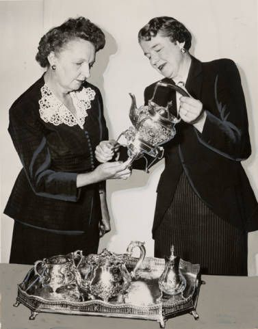 Encino Woman's Club members admire antique silver which was shown at the club's Heirloom and Treasures Show. The proceeds from the all day event went to the club to aid club work. Mrs. H. K. Winterer and Mrs. Kenneth Fitzpatrick are pictured here. This photograph was published in the Valley Times newspaper on April 11, 1950.  San Fernando Valley Historical Society. San Fernando Valley History Digital Library.: Admire Antique, April 11, Aid Club, Woman, 1950 San, Valley, Antique Silver, Digital