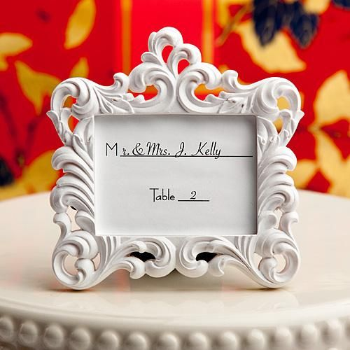 """Baroque Frame Wedding Place Card Holder made of white poly resin carved with an intricate scroll design. It has a black easel back so it easily stands on its own. Each frame includes a blank place card. It comes packaged in a white gift box. It arrives with an """"Especially For You"""" insert showing through the central window."""