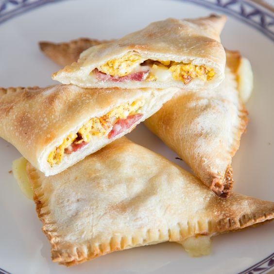 Frühstück ist fertig! Frisch gebacken und warm aus dem Ofen schmecken die saftig gefüllten Teigtaschen mit Rührei, Mozzarella, Parmesan und Chili am besten.