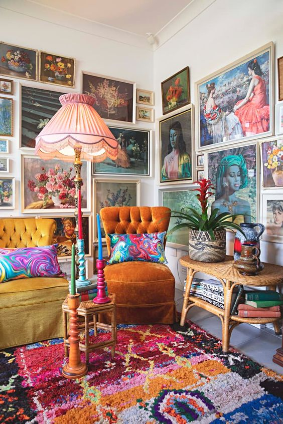 This maximalist bohemian space has plenty of colorful rugs, wall hangings, gallery walls and colorful chairs. We love the mid -century modern furniture combine with the bright textiles.