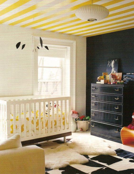 Kinderkamer met zwarte muur en gestreept plafond. Kinderkamers hoeven echt niet altijd zoete kleuren te bevatten. Deze kinderkamer heeft bijvoorbeeld een zwarte muur. Origineel is dat ook het plafond een kleur heeft gekregen! Domino