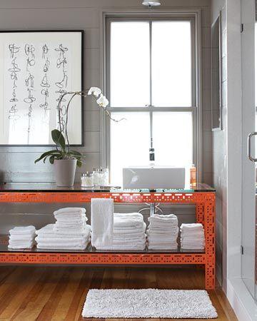 orange steel vanity + bright white stacks of towels