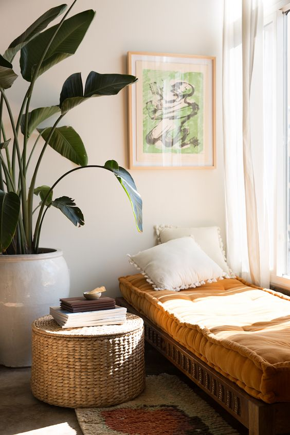 Daybed in the sun, can be used as extra bed for a guest. Plant and basket function as roomdivider.