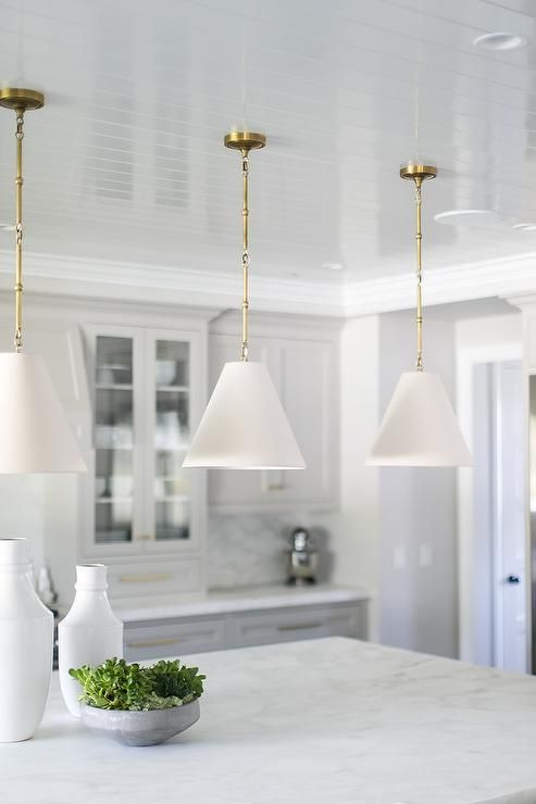 Glossy white beadboard ceiling flaunts white and gold Goodman hanging lamps in a white cottage kitchen.