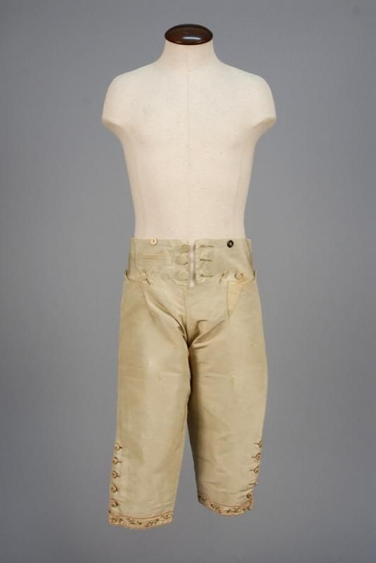 Breeches, 3-piece suit, c. 1775. Pale green faille having tambour embroidered floral garlands in rose, red and green on lattice ground, embroidered buttons, matching waistcoat and fall front breeches with white lining.