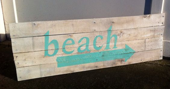 White 'Beach' sign, hand-painted lettering on pallet wood.