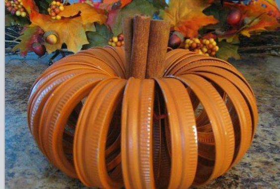 Mason jar lids spray painted orange, and tied together with cinnamon sticks in the middle.  Picture only.  From Crafts Corner.