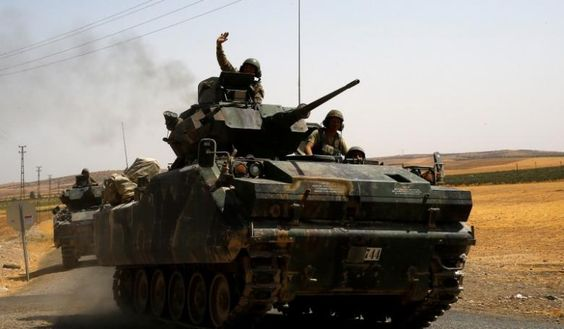 A Turkish soldier on an armoured personnel carrier waves as they drive from the…