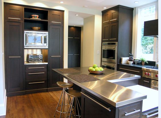 Stainless steel countertops brighten a kitchen with black cabinetry: