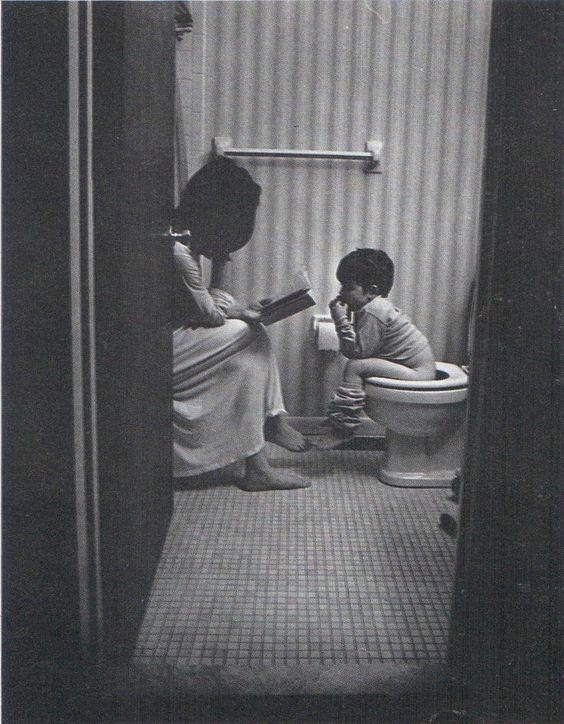 Mother and child heartwarming photo. Child on toilet.