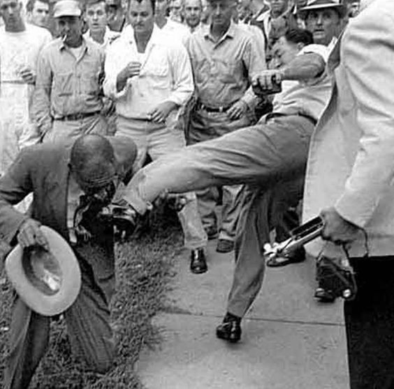 "Newspaper editor Alex Wilson of the Tri-State Defender of Memphis is  attacked by an angry mob of whites during the battle over integrating Central High School in Little Rock in 1957. ""I decided not to run,"" he wrote later. ""If I were to be beaten, I'd take it walking if I could—not running."""