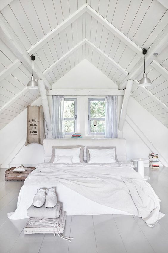 A pure white attic bedroom with an arched ceiling and two windows above the bed. Designed by http://jamkolektyw.com/:
