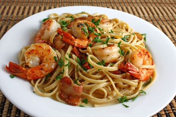 Shrimp Carbonara  Ingredients: 1 serving linguine 4 slices bacon (chopped) 1/4 pound shrimp (peeled and deveined) 1 clove garlic (chopped) pepper to taste 1 egg yolk 1 tablespoon heavy cream 1/4 cup parmigiano reggiano 1 tablespoon parsley (chopped)