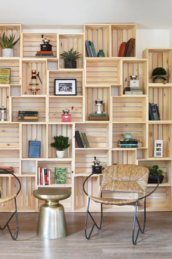 Une bibliothèque en caisses de bois rendue chic par une touche de doré, des fauteuils design et de beaux objets.:
