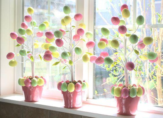 Trois petits pots à fleurs roses, garnis d'oeufs de Pâques tout autour, ont été déposés sur le rebord d'une fenêtre. Ces pots ont accueilli des arbres…