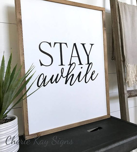 living room decor, stay awhile » size 21 x 27 » painted lettering » background color: white » lettering color: black » frame color: brown » this sign is made to be hung by the frame, there is no other hanging hardware installed » Our signs are made for interior decorating; no clear
