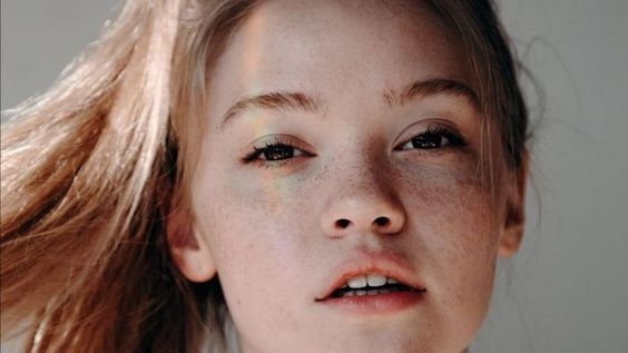 primer plano rostro chica pelirroja, rayo de sol en su cara