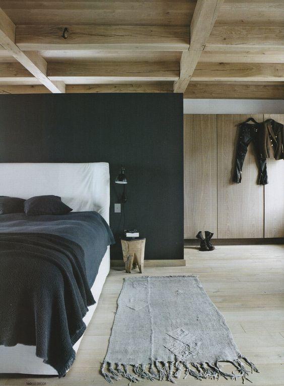 Une chambre dominée par le bois naturel et une cloison-tête de lit anthracite.