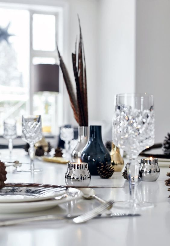 Simple christmas table setting in gold, silver, blue and white tones and with natural decorations.