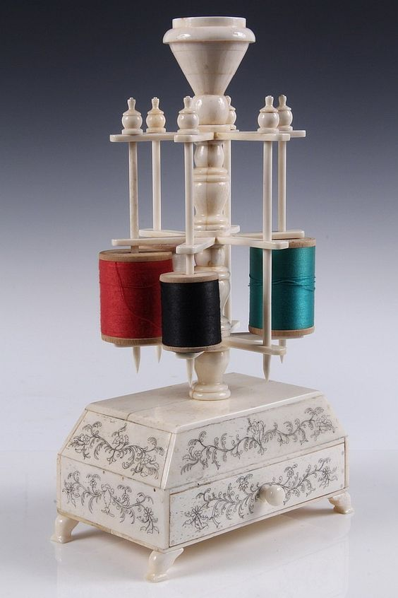 RARE SAILOR-MADE WHALEBONE SEWING STAND - Early 19th c Stand with rotating 6-spool thread holder, topped by pin cushion holder, set on canted base platform with single drawer, scrimshawn decoration. 6 x 3 1/4 at footed base. 10 3/8 tall. Pin cushion gone. Vintage 1840s J Coats ad folded in drawer.