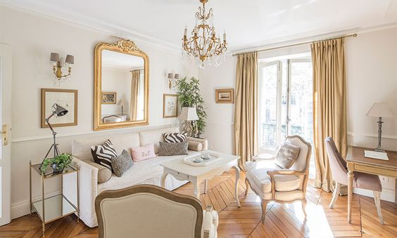 Gorgeous interior with romantic decor in a #Parisapartment with gold accents, herringbone floor, crystal chandelier, Bergere chairs and chic pillows.
