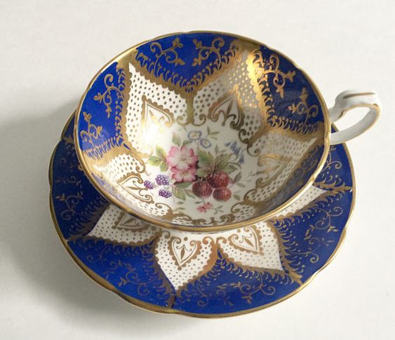 Vintage Paragon china tea cup and saucer, made in England. A lovely duo with lush gilding in blue with fruit and flowers on both the cup and saucer. It is in good condition, no chips, cracks or crazing. Please Note: The items I sell are not new, they are vintage or antiques, it