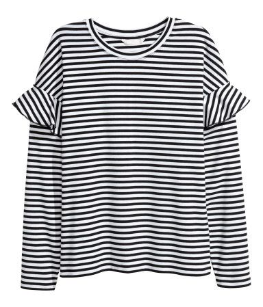 Black/white striped. Soft jersey top with long sleeves and dropped shoulders with a ruffle.