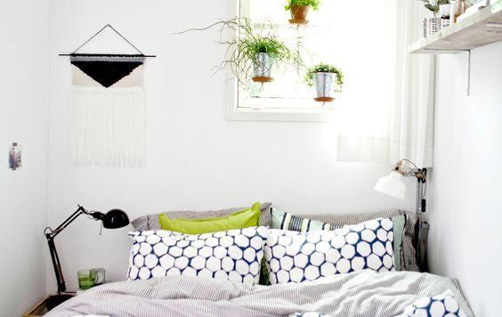 Weißes Schlafzimmer mit Textilien in kräftigen Farben und mit Hängepflanzen am Fenster