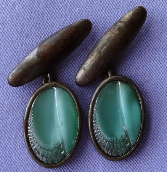 These fabulous cufflinks probably date from the 1920s or 1930s and bear lovely green glass stones with a superb Art Deco design.