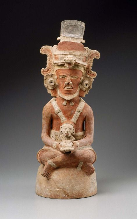 Human effigy incense burner top Maya Early Classic Period A.D. 400–550 Object Place: Department of El Petén, Guatemala, Tikal area A seated male figure, likely a Maya ruler, wears a zoomorphic headdress surmounted by a cartouche in which originally was painted his name (now eroded). He wears a large pectoral depicting a human face, which may represent the Maize god, and holds a human heart in his hands. Suspended from his nose is a crossed-bands and triangle icon. His body is paincartouche…