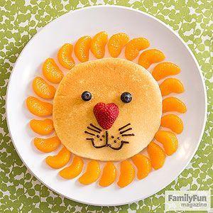 Panqueque en forma de león. Decorar con gajos de mandarinas (cuties), la mitad de una frutilla para la nariz, arándanos para los ojos y syrup de chocolate para la boca.