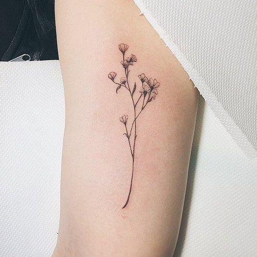 Minimalistic simple flower tattoo on inner arm