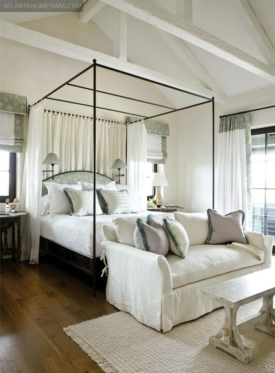 Canopy bed, loveseat at the foot, and architectural details.