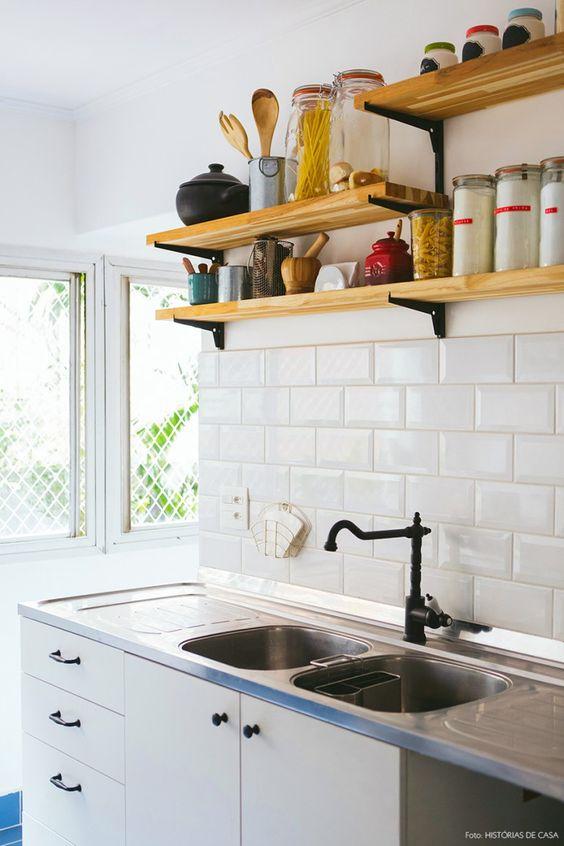 Cozinha com revestimento de azulejo de metrô, torneira preta e prateleiras pressas com mão francesa.