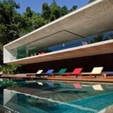 The Paraty House — not to be confused with Party House — was designed by Marcio Kogan Architects and is comprised of two concrete boxes that sit atop one another. The home is nestled in the mountainside of an island in Paraty, Brazil and residents have to arrive by boat.