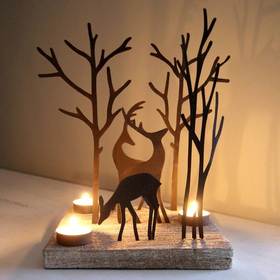 Tea light holder for cosy seasonal lighting. Reindeer woodland silhouette christmas decoration. Elegant and unusual tea light holder with a trio of rusty brown metal reindeers on a square whitewashed wooden base that suits contemporary or traditional settings. Creates lovely reflections once lit making it a treasured decoration sure to be enjoyed year after year. Tea lights not included.Metal and woodH28cm x L21cm
