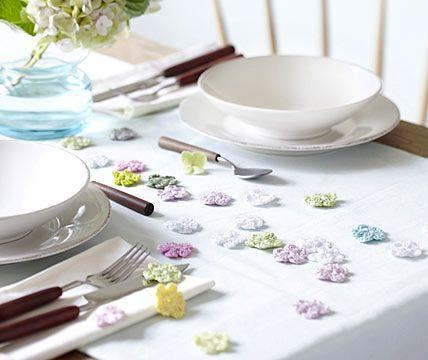 """Streublümchen  So schnell kann man aus einem schlicht in Weiß gedeckten Tisch eine Frühlingstafel machen: Gehäkelte bunte Streublümchen werden einfach fröhliche quer über dem ganzen Tisch verteilt. Und für die Gäste gilt: Pflücken und Mitnehmen erlaubt!     Gehäkelte Streublumen in allen Farben und Größen gibt es ab etwa 3 Euro (für 12 Stück) bei """"Garndesign"""" über Dawanda"""