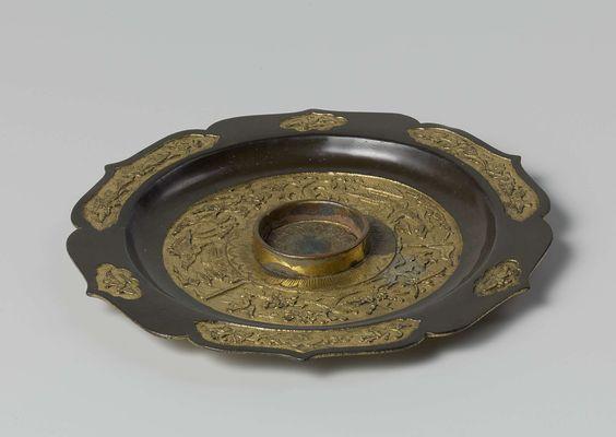 Anonymous | Schotel behorend bij het Tonkinservies, Anonymous, 1700 - 1800 | Schotel van vuurverguld suassa, met geschulpte accoladevormige rand en in het midden een opstaande ring, waarbinnen een kopje past. De rand heeft een gladde ondergrond zonder ingekerfde versieringen. Op bovenzijde van geschulpte accoladevormige rand zes cartouches (medaillons) met afbeeldingen in reliëf uitgestoken van takken met bloemen en vogels. Drie langwerpige en drie kleine ruitvormig geschulpte cartouches. Op…
