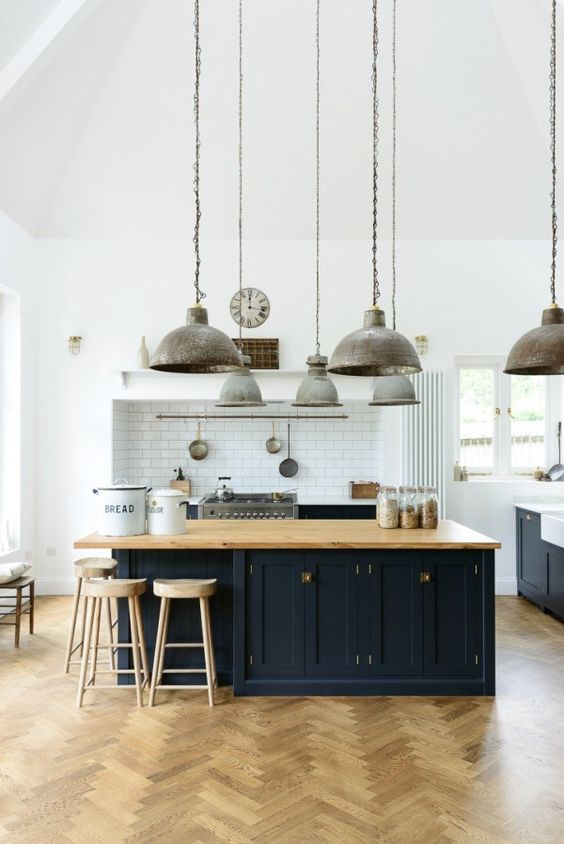 A stunning modern farmhouse kitchen designed by deVOL with multiple galvanized barn style pendant light suspended from lofty ceiling, herringbone wood flooring, and custom cabinetry. #modernfarmhouse #barnlight #deVOL