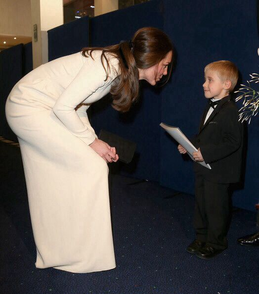 Catherine, Duchess of Cambridge meets a young boy in a dinner jacket as he attends the Royal film performance of 'Mandela: Long Walk to Freedom' at Odeon Leicester Square on December 5, 2013 in London, England.