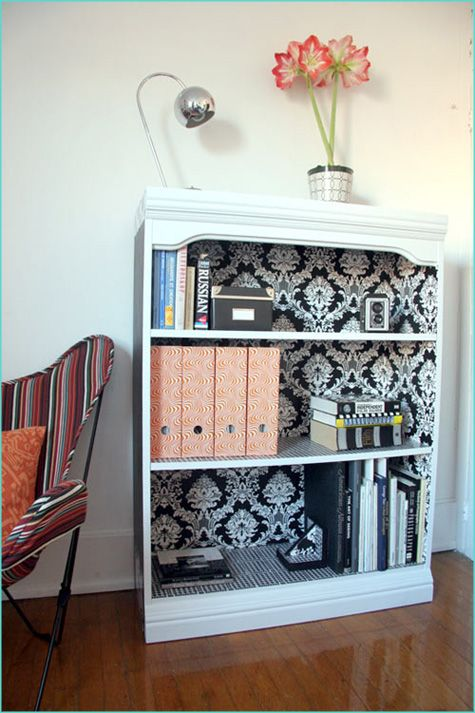 I could totally re-create this- just take those crummy bookcases from the discount store, add some molding trim pieces, paint and wallpaper the whole thing... very cute!