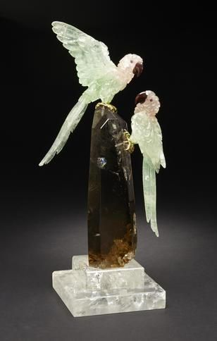 By Peter Mueller Brazil   This elegant pair of Macaws are each carved from a valuable bi-colored beryl known as morganite-green beryl, with a total approximate carats weights of 875.0 and 1154.0 carats.  With gold vermeil feet,  raised on a smoky quartz base, above a polished rock crystal quartz base.   Height 13in
