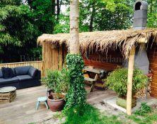 Een mooie en gezellige tuin, met een prachtige bamboe overkapping, welke is afgewerkt met palmblad
