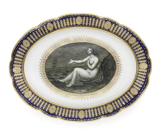 A rare Flight Worcester platter from the 'Hope' service, circa 1790 Made for the Duke of Clarence, the centre finely painted in monochrome by John Pennington with a seated figure of Hope gesturing towards a ship in full sail in the distance, an anchor at her feet, surrounded by an elaborate gilded formal band, the shaped border gilt with paterae and arched panels reserved on a blue ground gilt with stars, 48cm wide, crown, Flight and crescent mark in blue Footnotes      John Flight recorded…