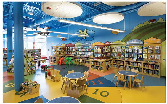 San José Public Library's Village Square Branch, CA, takes its young patrons seriously with a children's area entered through a colorful gateway with a clock tower; a small library-like building lets youngsters play librarian.:
