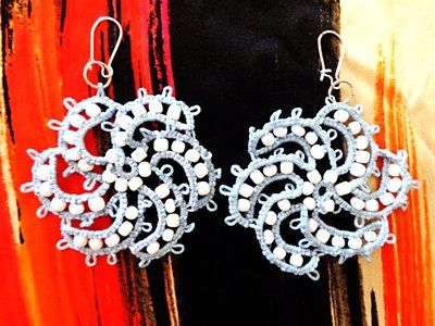 Spiral shaped earrings with white pearls made with tatting technique.