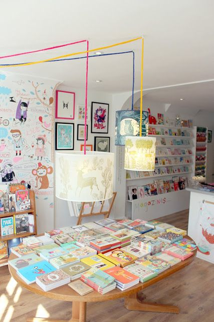comma shop interior bright, airy, lots of stock but not too cluttered, possible children's illustration theme?