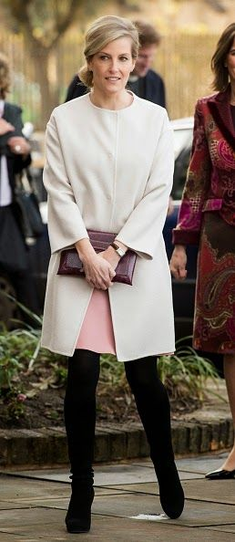 Sophie Countess of Wessex cut an elegant figure in her cream cocoon coat and powder pink dress, accessorizing her look with a burgundy clutch bag and suede knee high boots.