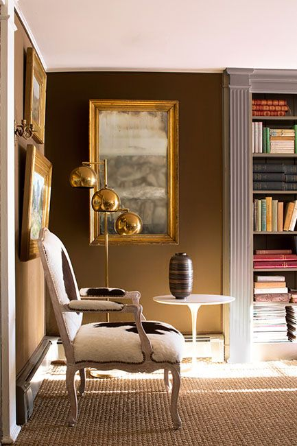 A living room with brown walls, a cowhide arm chair, gold framed mirror, sisal carpet Brown and bronze
