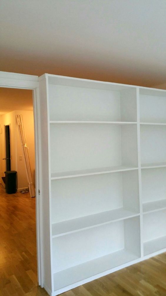 Bookcase wall with pocket door. Call us for all your custom room partition inquiries. (646) 837-7300